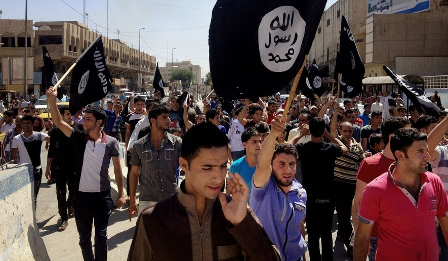 Demonstrators chant pro-Islamic State group slogans as they wave the group's flags in front of the provincial government headquarters in Mosul, Iraq, on June 16, 2014. (Associated Press)
