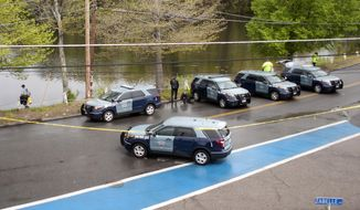 Massachusetts State Police divers search Stoneville Pond near the site where Auburn police Officer Ronald Tarentino Jr. was fatally shot during a traffic stop Sunday in Auburn, Mass. (Worcester Telegram & Gazette via Associated Press)