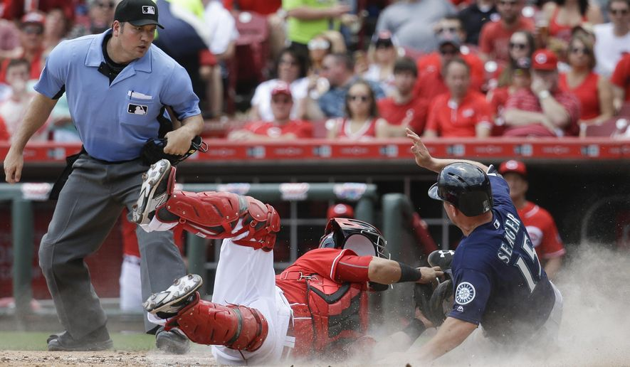 Seattle Mariners' Kyle Seager (15) is tagged out by Cincinnati Reds catcher Ramon Cabrera, center, at home plate in the fifth inning of a baseball game, Sunday, May 22, 2016, in Cincinnati. (AP Photo/John Minchillo)