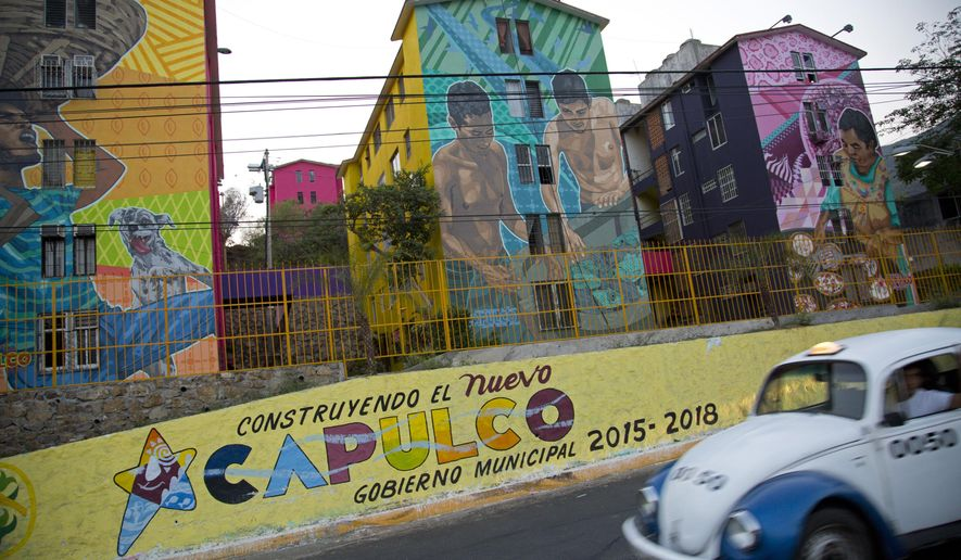 """In this May 11, 2016 photo, a taxi drives past the Cuauhtemoc Housing Unit and a municipal sign with a message that reads in Spanish; """"Building the new Acapulco"""" in Acapulco, Mexico. The city's latest wave of killings began April 24, when bursts of gunfire broke out along the coastal boulevard. The murder rate in this city of 800,000 hit 146 per 100,000 inhabitants in 2012. It has since fallen to about 112 per 100,000, but that remains far higher than nationwide levels. (AP Photo/Enric Marti)"""