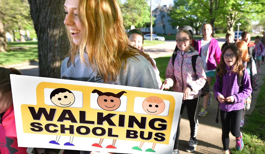 ADVANCE FOR THE WEEKEND OF MAY 21-22 AND THEREAFTER - Jacey Stratton, a Woodbury Central High School senior, leads a group of  Woodbury Central students as they walk to school Wednesday, May 4, 2016, as part of a walking school bus initiative at the Moville, Iowa, school. Participating students met the the city's park and walked approximately 5 blocks to the school building. (Tim Hynds/Sioux City Journal via AP)