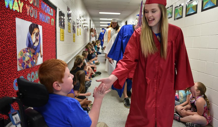 ADVANCE FOR MONDAY MAY 23 AND THEREAFTER - In this Friday May 13, 2016 photo, Herbert Hoover High School senior Kaitlin Mullins gives a high five to second-grader Andrew Bungard, of Pinch Elementary, in Elkview W.Va. About 20 Hoover seniors visited the school in their caps and gowns, to show the younger students the importance of graduating. (Kenny Kemp/Charleston Gazette/Mail via AP)