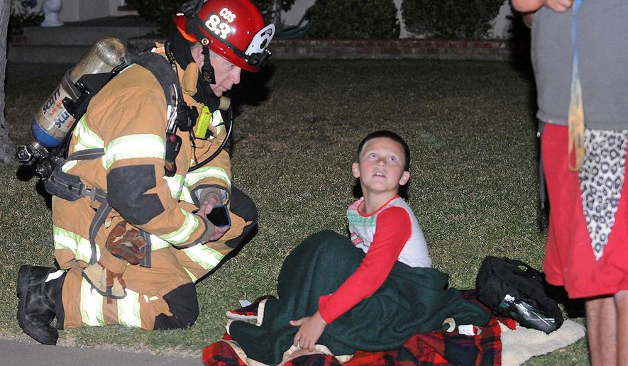 In this Saturday, May 21, 2016 photo, 7-year-old William Rimmer talks with Costa Mesa, Calif., Fire Department Capt. Chris Coates after the boy and his father escaped a fire that threatened their Cost Mesa home Saturday evening. Authorities say the boy didn't hesitate when he smelled smoke at his home, waking up his sleeping father so the pair could escape a spreading fire. The fire was confined to the home's garage.(AP Photo/Richard Koehler)