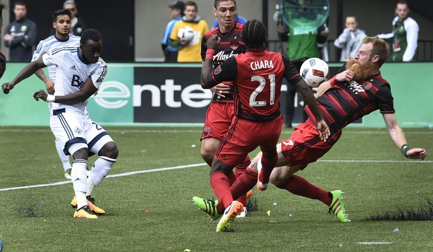 Vancouver Whitecaps forward Kekuta Manneh (23) has his shot blocked by Portland Timbers defender Nat Borchers (7) during the first half of an MLS Soccer game in Portland, Ore., on Sunday, May. 22, 2016.(AP Photo/Steve Dykes)