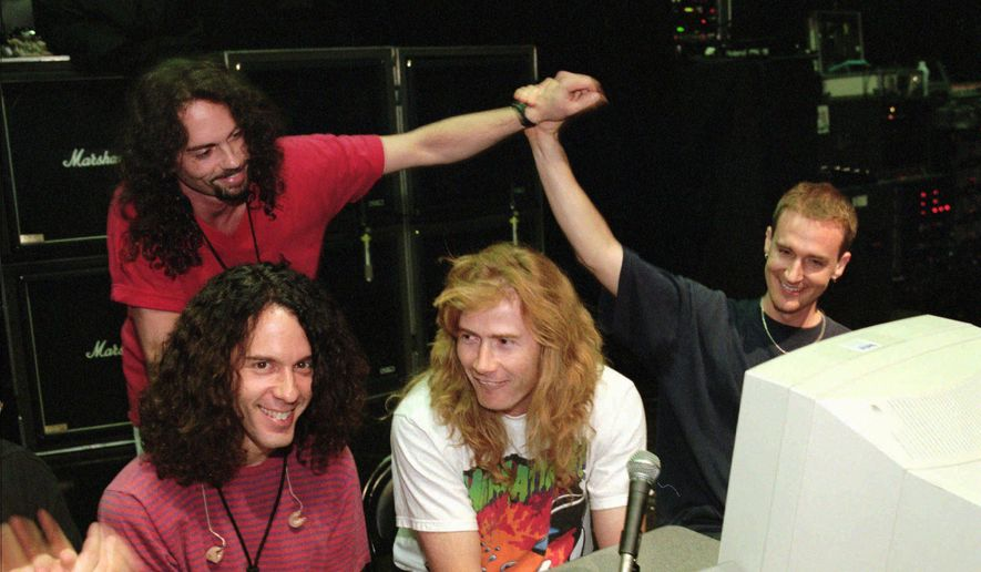 In this July 24, 1997, file photo, lead guitarist Marty Friedman, left, and lead singer/guitarist Dave Mustaine, center, field questions while bassist David Ellefson, right, high-fives drummer Nick Menza, back left, during a live chat on the internet held at The Joint inside the Hard Rock hotel-casino in Las Vegas. (Ethan Miller/Las Vegas Sun via AP)