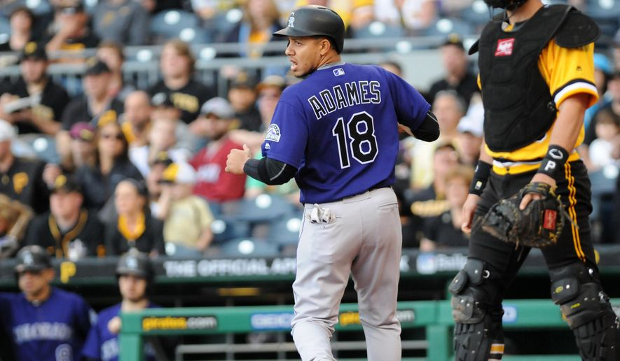 Colorado Rockies short stop, Cristhian Adames, left, looks back after crossing the plate and scoring the first run of the game in the first inning against the Pittsburgh Pirates during a baseball game Sunday, May 22, 2016, in Pittsburgh. (AP Photo/John Heller)
