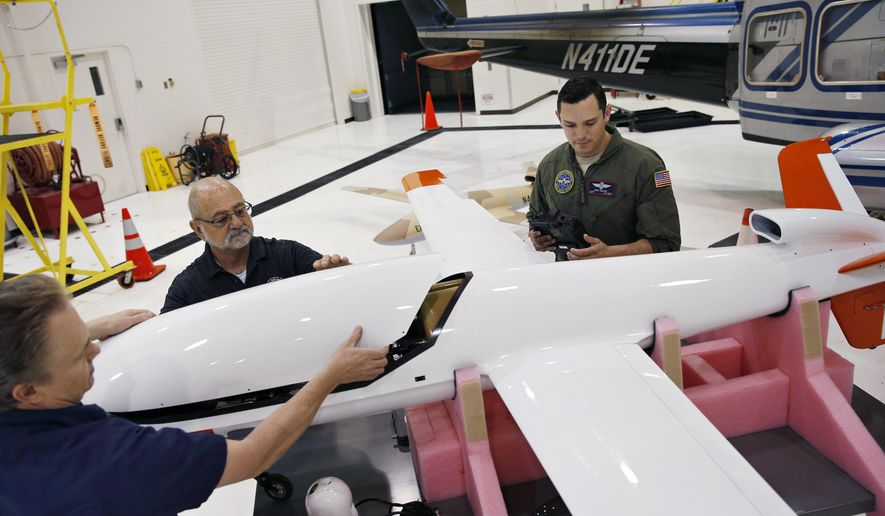 In this May 19, 2016, photo, Joe Cummings, from left, Mike Lukens and Mike Toland, of National Security Technologies, a contractor for the National Nuclear Security Administration, work on a drone at the Remote Sensing Laboratory in Las Vegas. Officials from the Nevada National Security Site announced the purchase of two unmanned aerial vehicles as part of a test program to provide arial radiological monitoring in the event of an emergency. (AP Photo/John Locher)