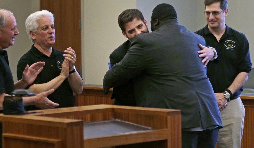 In this May 13, 2016 photo, Mentor William Delaney, a former U.S. Marine, embraces a fellow Marine who just completed a treatment program at the Kent County Courthouse in Warwick, R.I. The Veterans Treatment Court opened five years ago in Warwick as the first specialty court in New England to help veterans avoid jail and turn their lives around. Delaney now is a mentor for veterans in the program. Flanking Delaney are retired veterans who also serve as mentors. (AP Photo/Charles Krupa)