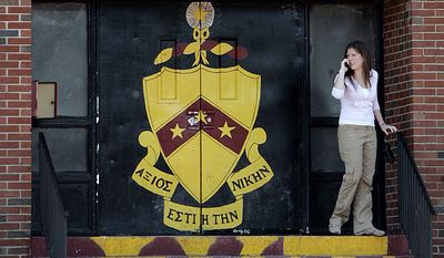 A young woman talks on a cellular telephone as she stands on the steps of the Phi Kappa Tau fraternity dorm on the campus of Rider University in Lawrenceville, N.J., on March 30, 2007. A freshman died after excessive drinking at the fraternity house on the university's campus. (Associated Press) **FILE**
