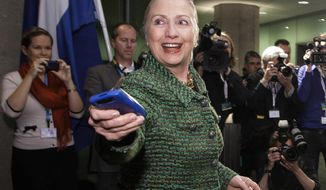 In this Dec. 8, 2011, photo, then-Secretary of State Hillary Rodham Clinton hands off her mobile phone after arriving for a meeting in The Hague. FBI agents probing whether Hillary Clinton's use of a private email server imperiled government secrets appear close to completing their work, a process experts say will likely culminate in a sit-down with the former secretary of state. (Associated Press) **FILE**
