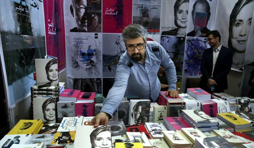 """In this picture taken on Tuesday, May 10, 2016, a book seller arranges U.S. presidential candidate Hillary Clinton's book """"Hard Choices"""" translated to Persian during Tehran's International Book Fair in Iran. Iranians have some concerns about Democratic frontrunner Clinton, who many consider to have struck a relatively hard line on Iran during her time as Secretary of State. (AP Photo/Vahid Salemi) ** FILE **"""