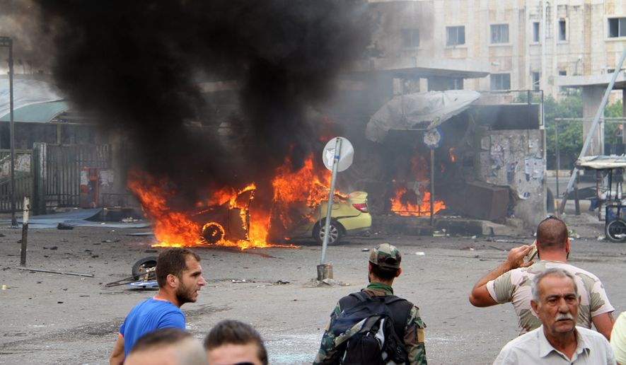 In this photo released by the Syrian official news agency SANA, Syrians gather in front of a burning car at the scene where suicide bombers blew themselves up, in the coastal town of Tartus, Syria, Monday, May 23, 2016. The Syrian TV said suicide bombers blew themselves followed by a car bomb in a parking lot packed during morning rush hour. (SANA via AP)