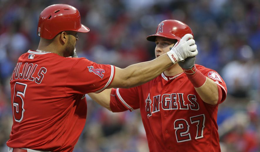 Los Angeles Angels Albert Pujols (5) celebrates his two run homer with teammate Mike Trout (27) during the third inning of a baseball game against the Texas Rangers in Arlington, Texas, Monday, May 23, 2016. (AP Photo/LM Otero)
