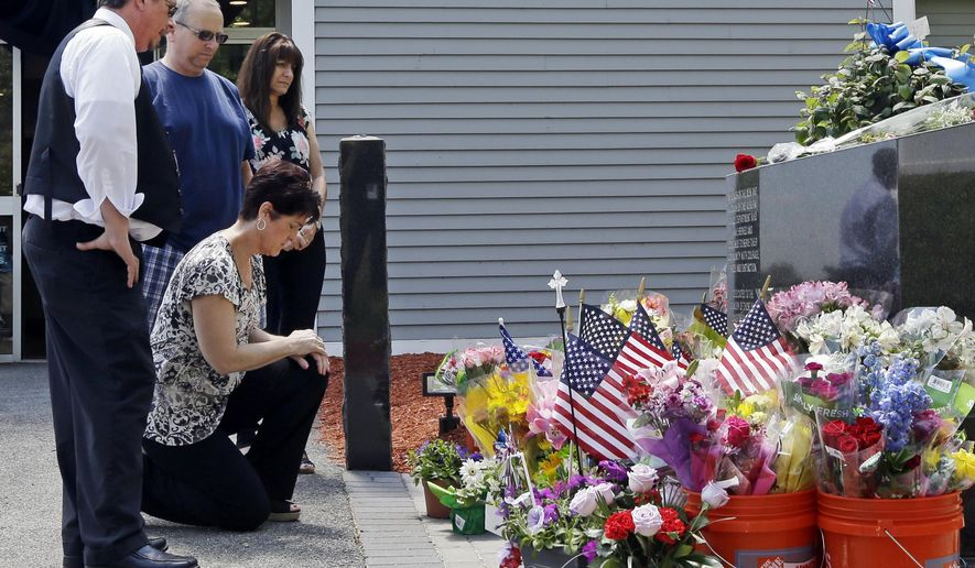 Mourners, including Jennifer Bohn, kneeling, her husband Randy Bohn, center, and Scott Veau, left, pause before a memorial set up for slain police Officer Ronald Tarentino outside the police station, Monday, May 23, 2016, in Auburn, Mass. Tarentino was fatally shot during a traffic stop in Auburn on Sunday morning, authorities said. (AP Photo/Elise Amendola)