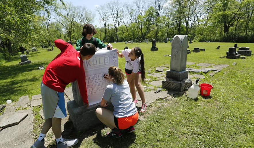Riley Meyer, clockwise from bottom, Eliot Champion, Michael McKee and Molly Cromer create a rubbing of the marker for John Kolb and his wife, Jemima, Wednesday, May 18, 2016, in the Pierce Cemetery behind Harrison High School in West Lafayette, Ind. Students are cleaning markers and doing other repair work for the Pierce Cemetery restoration project in Ashley Greeley's advanced placement U.S. history class at Harrison. (John Terhune/Journal & Courier via AP)