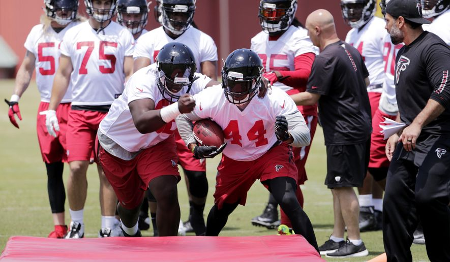 Atlanta Falcons' Joey Mbu, left, tries to knock the ball away from Vic Beasley Jr., during a drill at an NFL football practice Monday, May 23, 2016, in Flowery Branch, Ga. (AP Photo/David Goldman)