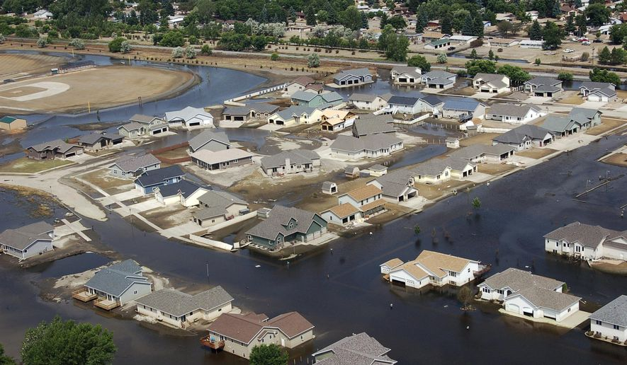FILE - This July 13, 2011 file photo shows homes flooded by the Souris River in Minot, N.D. Work is beginning on local flood protection projects in the Souris River Basin while officials await the outcome of studies on long-term flood protection. The flooding in June 2011 caused by heavy spring snowmelt and rains caused more than $700 million in damage in the region. (AP Photo/James MacPherson, File)