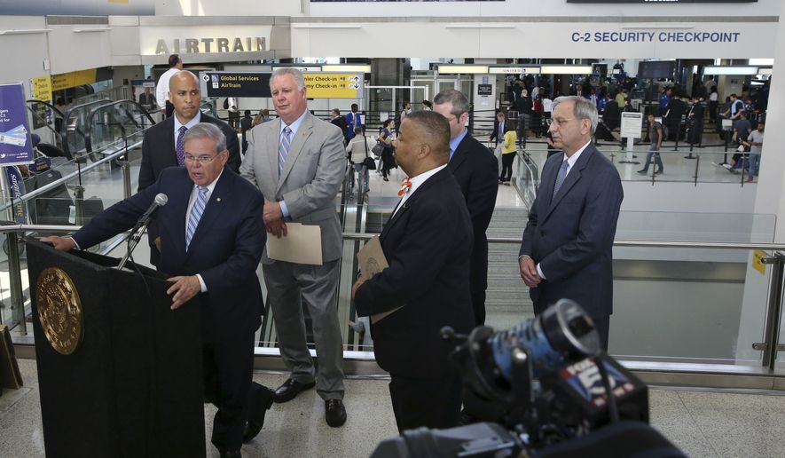As Sen. Cory Booker, back left, D-N.J., Rep. Albio Sires, D-N.J., back second from left, Rep. Donald Payne Jr., third  from right, D-N.J., and others listen, Sen. Bob Menendez, D-N.J., front left, announces the Transportation Security Administration is adding 100 agents by next month, Monday, May 23, 2016, in Newark, N.J. (AP Photo/Mel Evans)