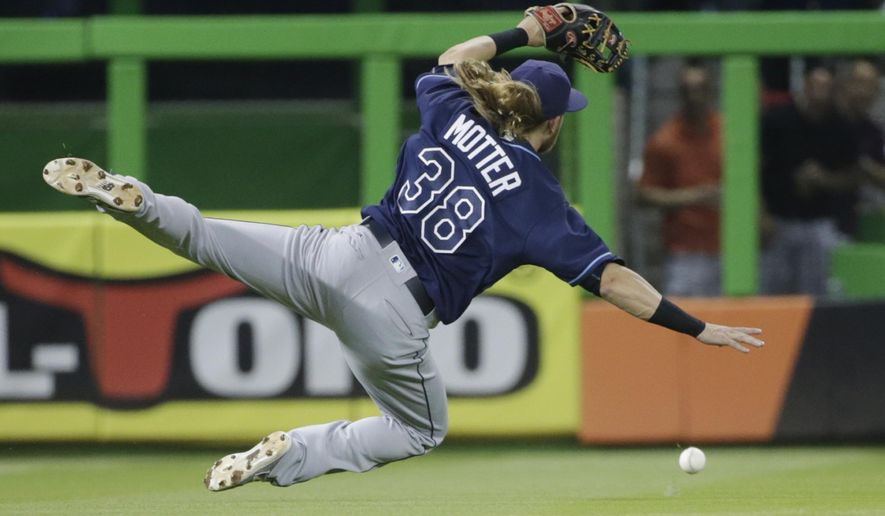 Tampa Bay Rays short stop Taylor Motter is unable to catch a ball hit by Miami Marlins' Miguel Rojas during the first inning of a baseball game, Monday, May 23, 2016, in Miami. Rojas reached first base scoring Martin Prado and Marcell Ozuna. (AP Photo/Wilfredo Lee)