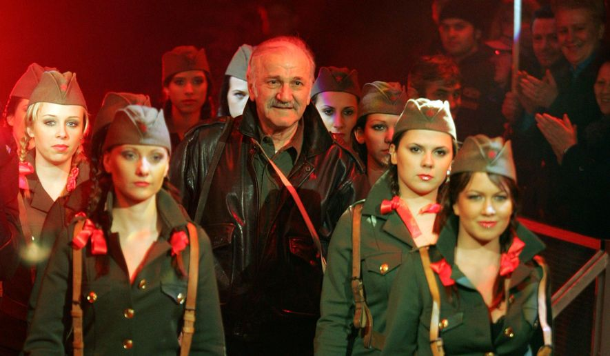 """In this photo taken March 1, 2008, Velimir Bata Zivojinovic, former Yugoslavia's best known film star who was also popular in China arrives for a media event flanked by model dressed in Yugoslav partizan military uniforms. Zivojinovic died late on Sunday, May 22, 2016, in a Belgrade hospital. His most famous movie, """"Walter Defends Sarajevo,"""" made Zivojinovic a star in China. (AP Photo/Andrej Cukic)"""