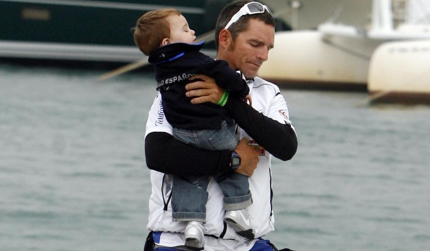 """FILE - In this Oct. 11, 2008 file photo, Telefonica Black skipper Fernando Echavarri from Spain takes his son onto the yacht before the start of the Volvo Ocean race in Alicante, Spain. Spain's Olympic gold-medal winning sailor says he's """"lucky to have survived"""" after being robbed at gunpoint in Rio de Janeiro as he and two fellow Spaniards were walking to breakfast. Echavarri spoke the Associated Press on Monday, May 23, 2016, three days after the assault, and says """"we were confident, but being confident in Rio is not a good thing."""" Echavarri and members of the Spanish team have been training in Rio for almost two weeks, preparing for South America's first Olympics. (AP Photo/Alberto Saiz, File)"""