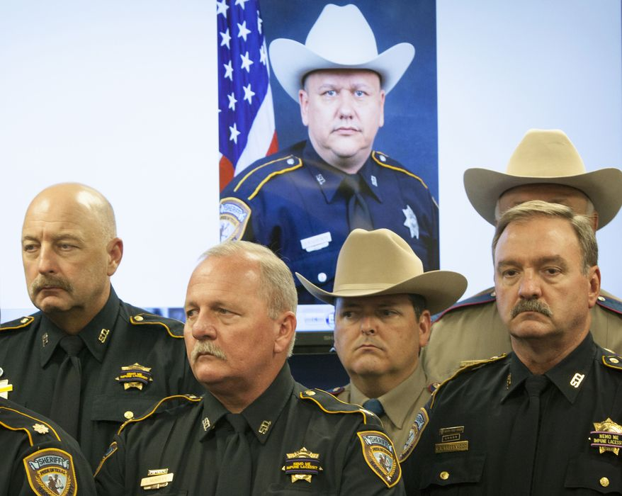 Law enforcement officers attend a Aug. 29, 2015, news conference in Houston on the shooting death of Harris County Sheriff's Deputy Darren Goforth, pictured in the background. (Marie D. De Jesus/Houston Chronicle via Associated Press) **FILE**