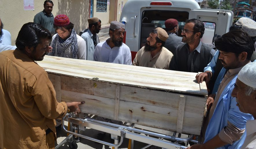 People stand near a coffin carrying a body one of the victims of a U.S. drone strike on May 22 in Quetta, Pakistan. A senior commander of the Afghan Taliban confirmed that the extremist group's leader, Mullah Mohammed Akhtar Mansour, was killed in the  strike. (Associated Press)