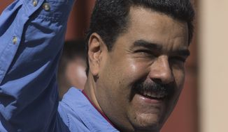 Venezuela's President Nicolas Maduro gestures to supporters during a women's march for peace at Miraflores Presidential Palace in Caracas, Venezuela, Tuesday, May 24, 2016. Maduro is facing a movement by the opposition to force a referendum to recall him from office. (AP Photo/Ariana Cubillos)