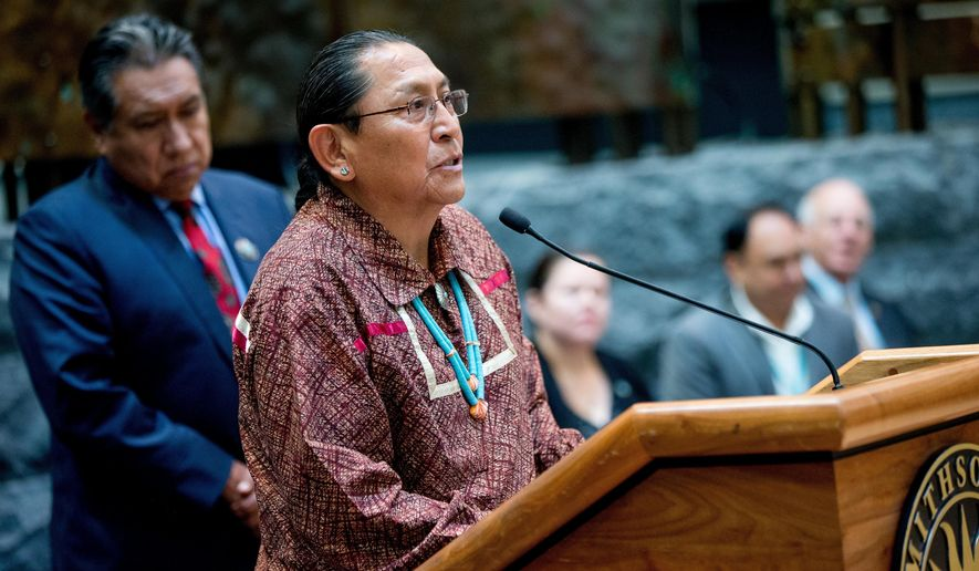 Pueblo of Acoma Gov. Kurt Riley, center, accompanied by Pueblo of Acoma Traditional Leader Conroy Chino, left, speaks as a group of American Indian Nations and American Indian advocates hold a news conference at the Smithsonian National Museum of the American Indian, in Washington, Tuesday, May 24, 2016, to contest a Paris auction house's upcoming auction of Native American remains and sacred objects. The items are slated to be sold by the EVE auction house in Paris on May 30. (AP Photo/Andrew Harnik)