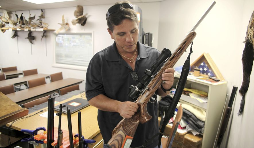 FILE - In this May 10, 2016, file photo, Jerry Ilo holds a gun that he uses to teach the Hawaii Department of Natural Resources hunter education training course in a classroom in Honolulu. Ilo was one of several Hawaii residents to speak out against a bill passed by lawmakers to allow Hawaii gun owners to be registered in a federal database that will automatically notify police if an island resident is arrested anywhere else in the country. (AP Photo/Marina Riker, File)
