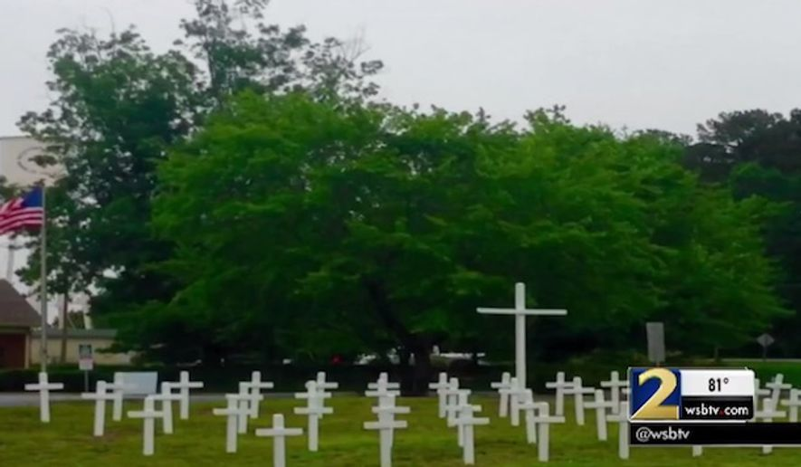 A Memorial Day display featuring dozens of white crosses to honor fallen soldiers was removed from public property in Georgia after someone complained. (WSB-TV)