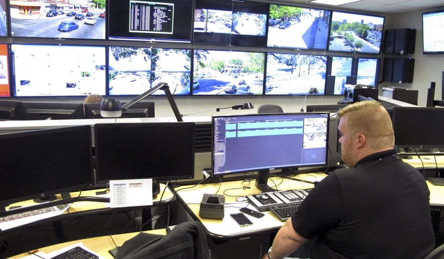 In this Friday, May 20, 2016 photo, Tyler Cullen, of Vulcan Security Technologies, looks at video screens in the Hartford police Real-Time Crime and Data Intelligence Center in Hartford, Conn. Staff at the center analyze data from surveillance cameras, gunshot detectors, license plate scanners and other sources. Vulcan Security Technologies helped set up the center. Such facilities are proliferating nationwide with the expanded use of surveillance technology, raising some concerns from civil liberties advocates. (AP Photo/Dave Collins)