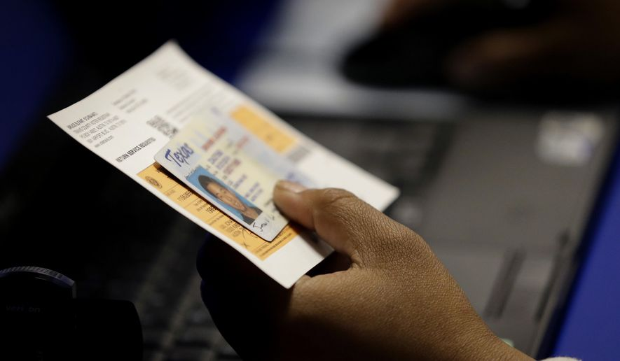 An election official checks a voter's photo identification at an early voting polling site in Austin, Texas, on Feb. 26, 2014. (Associated Press) **FILE**