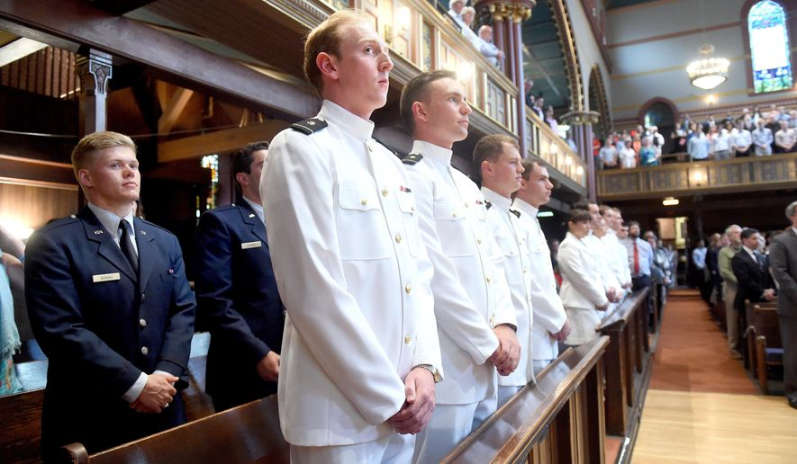 Navy Ensign Eric Abney, center, and the other graduates of the Air Force and Naval ROTC program at Yale University attend the Joint Military Commissioning Ceremony at Yale University's Battell Chapel in New Haven, Conn., Monday, May 23, 2016. Defense Secretary Ashton Carter handed out commissions Monday to the Yale's first ROTC graduating class in more than four decades. (Arnold Gold/New Haven Register via AP) MANDATORY CREDIT