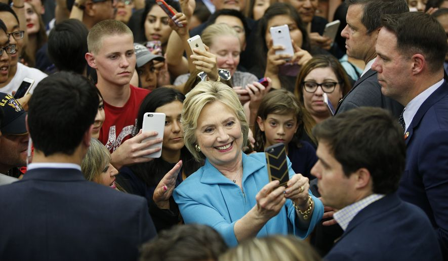 Democratic presidential candidate Hillary Clinton poses for selfies at a rally at the University of California, Riverside, Tuesday, May 24, 2016, in Riverside, Calif. (AP Photo/John Locher)