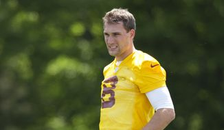Washington Redskins starting quarterback Kirk Cousins (8) looks at the field as they stretch during NFL football practice at the Redskins Park in Ashburn, Va., Wednesday, May 25, 2016. (AP Photo/Manuel Balce Ceneta)