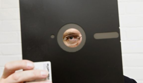 In this Nov. 16, 2004, file photo, an obsolete 8 and 1-half-inch floppy disk is held in London. (AP Photo/Adam Butler, File)
