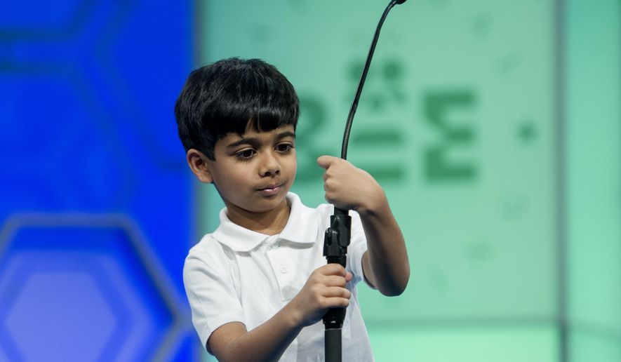 Akash Vukoti, 6, of San Angelo, Texas, tries to shorten the microphone before spelling his word during the preliminary round two of the Scripps National Spelling Bee in National Harbor, Md., Wednesday, May 25, 2016. Vukoti is the youngest speller in this year competition. (AP Photo/Cliff Owen)