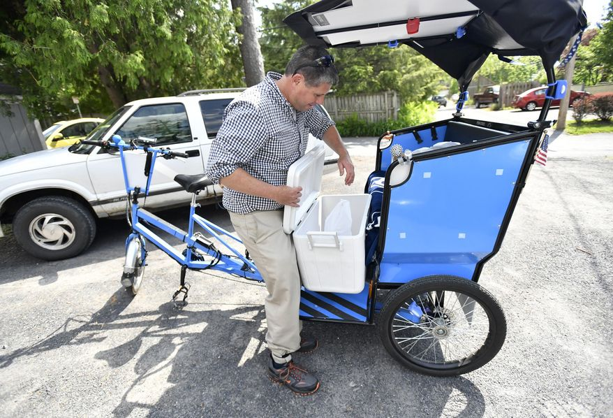 "ADVANCE FOR WEEKEND EDITIONS - In this Tuesday, May 24, 2016 photo, Todd Miner loads food onto his bicycle to be delivered in State College, Pa. The Friends and Farmers Cooperative Online Market hosted a Bike Delivery Day. The bicyclists made deliveries of locally grown food to customers who specified ""deliver by bike."" (Nabil K. Mark/Centre Daily Times via AP) MANDATORY CREDIT"