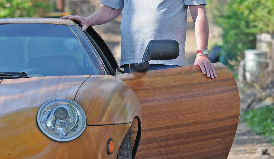 In this May 8, 2016 photo,  Ken Ryan stand next to a wooden car he built in Bismarck, N.D. Ryan couldn't believe the attention his wooden car attracted when he drove it from the Canadian border at Antler to the Gulf of Mexico and back to North Dakota. Twenty years ago, Ryan bought a 1985 Pontiac Fiero, replaced all but the frame to make the wooden car that's street-legal today.  (Tom Stromme/The Bismarck Tribune via AP) MANDATORY CREDIT