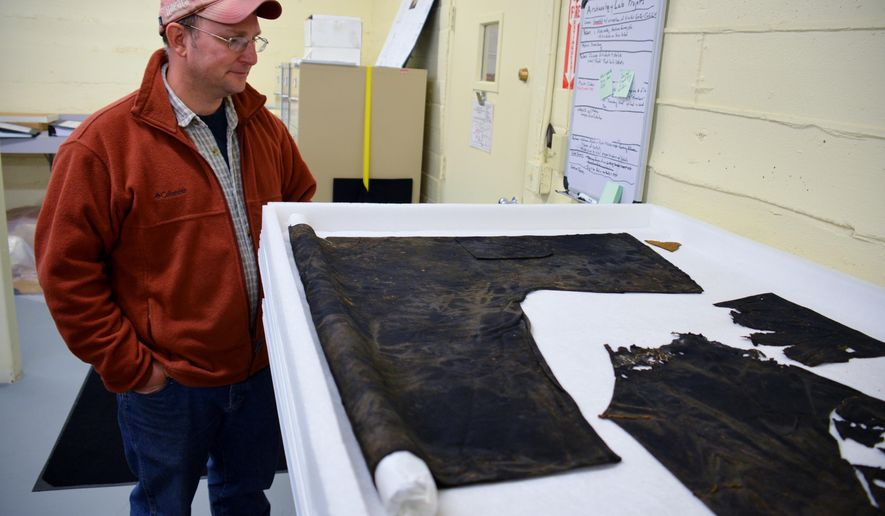 ADVANCE FOR MONDAY MAY 30 AND THEREAFTER - In an April 26, 2016 photo, archivist Mike Runge looks over an authentic Chinese garment used in burial rituals that was unearthed during a Chinatown dig in Deadwood and recently hydrated and cleaned. The 2001 discovery has become one of Deadwood's Archive Department's most telling artifacts from a special subculture who dwelled in the city during its earliest days. (Jaci Conrad Pearson/ Black Hills Pioneer via AP)