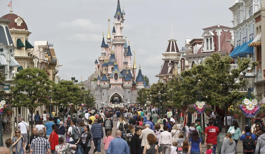 """FILE - In this May 12, 2015, file photo, visitors walk near Sleeping Beauty's Castle at Disneyland Paris, in Marne la Vallee, east of Paris. The Euro Disney group is going on trial in France, Wednesday May 25, 2016, for publishing an allegedly discriminatory job ad requesting that candidates have """"European citizenship"""" to work as parade artists at its famous Disneyland Paris theme park. (AP Photo/Michel Euler, File)"""