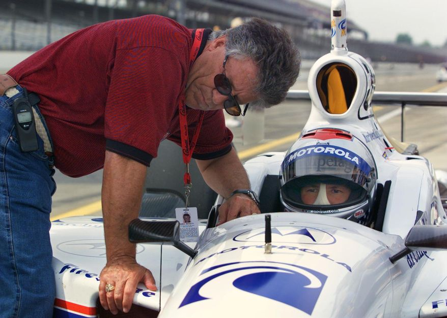 "FILE - In this May 10, 2001, file photo, Mario Andretti, left, chats with his son Michael during practice at Indianapolis Motor Speedway in Indianapolis. In the lead-up to the 100th running of the ""The Greatest Spectacle in Racing,"" The Associated Press interviewed the 27 living race winners on topics ranging from the greatest driver to most memorable moment. Their answers to the best driver to never win the Indianapolis 500 gave Michael Andretti a distinction he'd rather go to anyone else.  (AP Photo/Michael Conroy, File)"