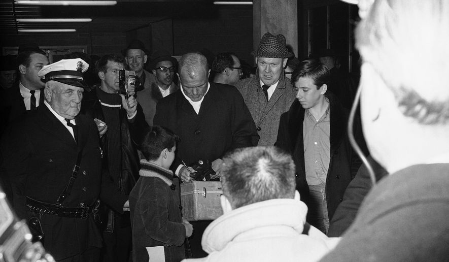 FILE - In this Jan. 17, 1964, file photo, astronaut John Glenn, center, signs an autograph before announcing his first bid to seek the Democratic nomination to run for U.S. senator of Ohio, as reporters and photographers document his arrival at Port Columbus airport in Columbus, Ohio. State lawmakers in Ohio voted Wednesday, May 25, 2016, on a bill that would honor the 94-year-old former astronaut and Democratic U.S. senator by renaming the facility as John Glenn Columbus International Airport. (AP Photo, File)