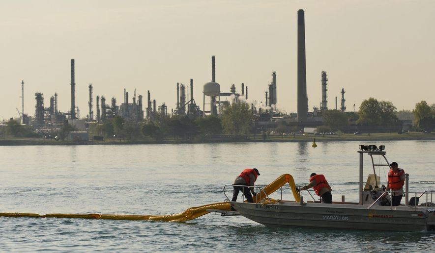 In this file photo, Enbridge Energy pipeline maintenance crews place an oil containment boom in the St. Clair River during a oil spill practice drill in Marysville, Mich. on Wednesday May 25, 2016.   (Tanya Moutzalias/MLive Detroit via AP) **FILE**