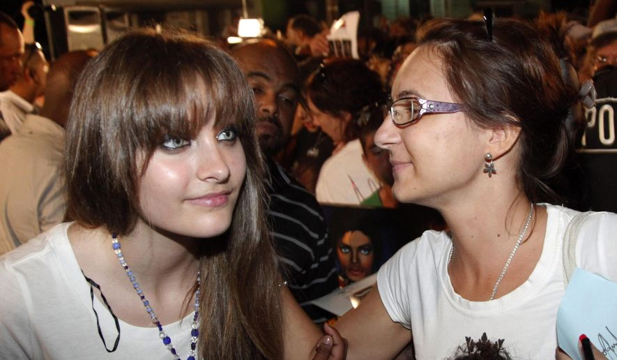 This Aug. 29, 2012, file photo shows Paris Jackson, left, daughter of the late pop icon Michael Jackson, poses with a fan outside Jackson's boyhood home during a celebration on what would have been Jackson's 54th birthday in Gary, Ind. Jackson revealed a new tattoo on May 23, 2016, that honors her father. (AP Photo/Charles Rex Arbogast, File)