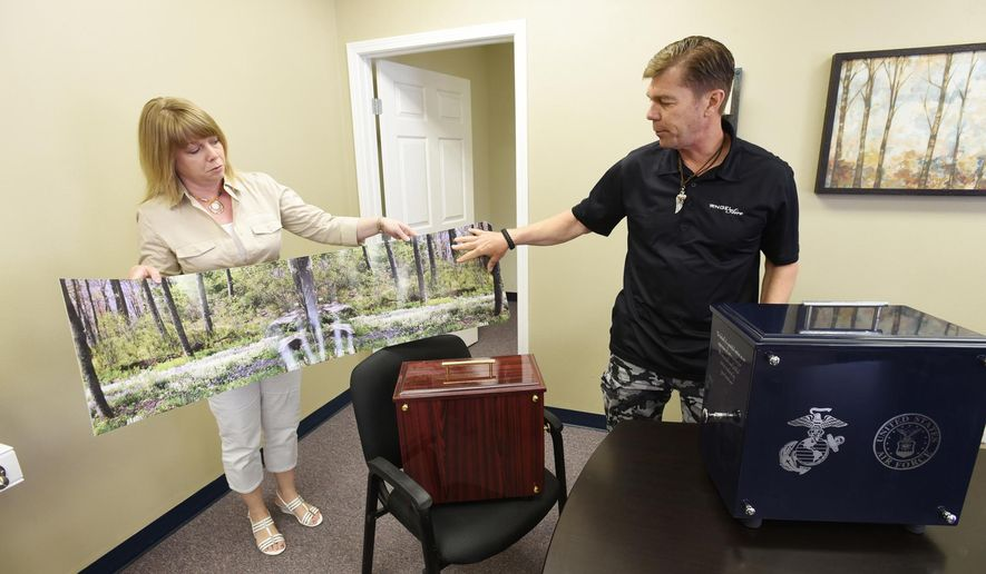 In this May 11, 2016, Scotty Crandlemire, right, inventor of the Angel Aire urn, and Angle Aire franchisee Sarahlee Ziesins, left, display a custom cover that can wrap around the urn that has a build in fan that scatters ashes at the new Caldwell, Idaho business. (Greg Kreller/Idaho Press-Tribune via AP)