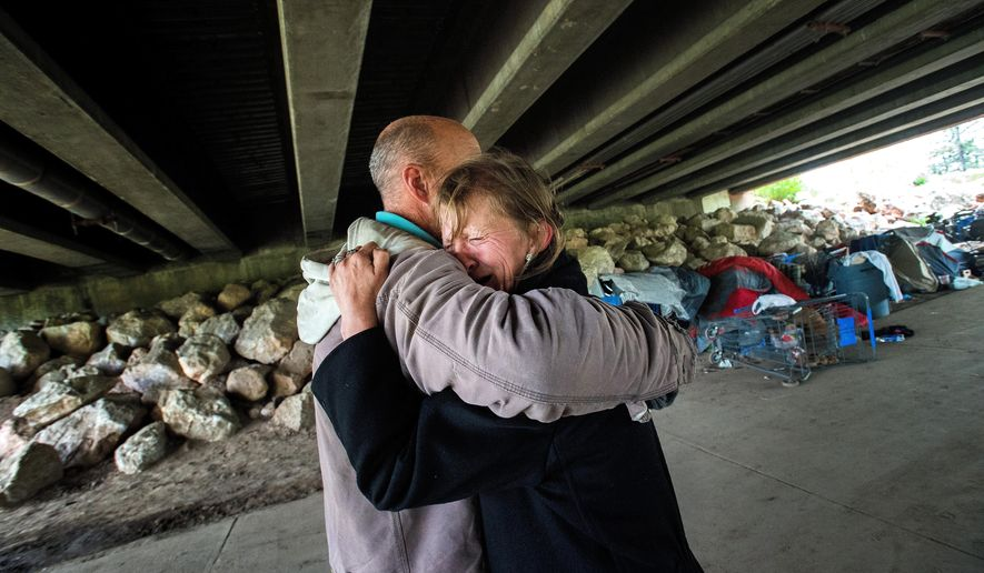 In this Wednesday, May 18, 2016 photo, Darin Taylor hugs Kathy Baker under the Tejon Street bridge in Colorado Springs, Colo., after she was reminded of the 2015 assault that left her husband, Terry Cagle, with a severe brain injury, leading to them to become homeless. (Christian Murdock/The Gazette via AP) MAGS OUT; MANDATORY CREDIT