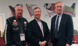 Tim Hussey, CEO of Hussey Seating Co., stands between Maine Sen. Angus S. King Jr. (right) and Rolling Thunder leader Joe D'Entremont with a POW/MIA commemorative chair. The family-owned company, based in North Berwick, Maine, is a partner in the effort to place these chairs in public venues as a reminder of veterans who are missing or held captive. (Hussey Seating Co.)