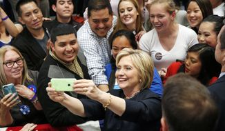 Democratic presidential candidate Hillary Clinton takes a selfie with supporters at a rally, Thursday, May 26, 2016, in San Francisco. (AP Photo/John Locher) ** FILE **